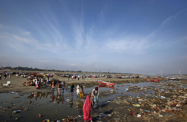 Indian Hindu devotees cross the polluted water of Ganges River at Sangam, the confluence of the Ganges, Yamuna, and the mythical Saraswati River, in Allahabad, India, Monday, April 22, 2013. April 22 is observed as Earth Day every year as a tool to raise ecological awareness. (Photo by Rajesh Kumar Singh/AP Photo)