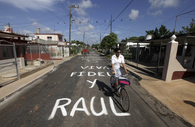 "A woman rides her bicycle on a road that reads ""Long live Fidel and Raul"" in Artemisa province, near Havana July 25, 2014. (Photo by Enrique de la Osa/Reuters)"