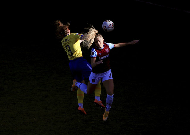 Brighton and Hove Albion's Felicity Gibbons, left, and West Ham United's Alisha Lehmann are caught in sunlight, competing for a header during their Women's Super League soccer match at Chigwell Construction Stadium, in London, Sunday November 15, 2020. (Photo by Mike Egerton/PA Wire via AP Photo)