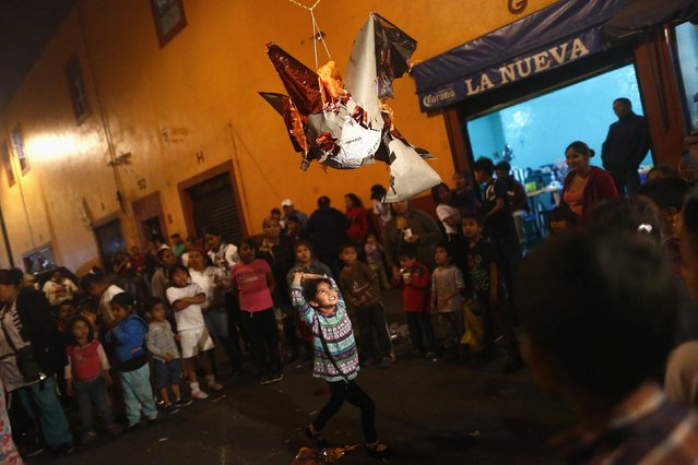 """A girl prepares to hit a pinata during a traditional Mexican Christmas celebration known as """"Posada mexicana"""" at La Merced neighbourhood in Mexico City December 17, 2014. Posada Mexicana is a pre-Christmas celebration to commemorate the journey of the Holy Family from Galilee to Bethlehem. (Photo by Edgard Garrido/Reuters)"""