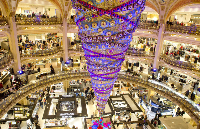 A christmas tree stands at the center of the department store Galeries Lafayette in Paris, France on Monday , December 8, 2014. The decorations are traditionally put up late November each year for Christmas. (Photo by Jacques Brinon/AP Photo)
