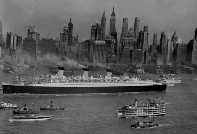 The mighty Queen Mary shown as she edged up lower New York Harbor, with the skyline of Manhattan in the background, toward her pier and the completion of her first voyage to the United States, June 1, 1936. (Photo by AP Photo)