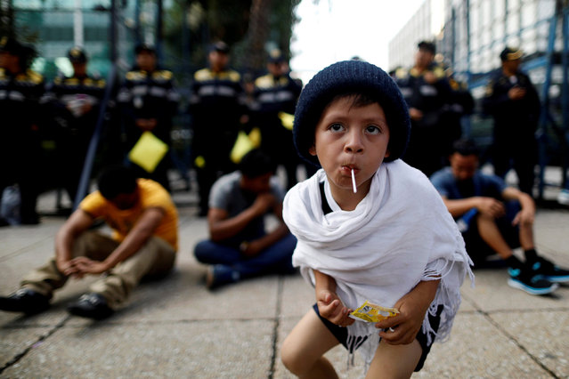 A migrant boy from Central America, moving in a caravan through Mexico, sucks a lollipop during a demonstration outside the U.S. Embassy in Mexico City, Mexico April 12, 2018. (Photo by Edgard Garrido/Reuters)
