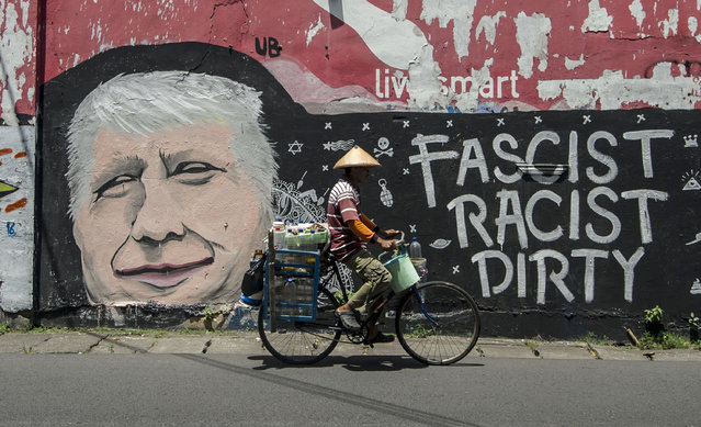 A man cycles past graffiti condemning US Republican presidential nominee Donald Trump, on a street in Surabaya, Indonesia's east Java on October 17, 2016. (Photo by Juni Kriswanto/AFP Photo)
