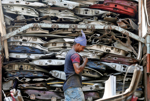A worker adjusts a button on his T-shirt as he loads used car doors onto a truck at a scrap yard in Mumbai, India, October 20, 2016. (Photo by Shailesh Andrade/Reuters)