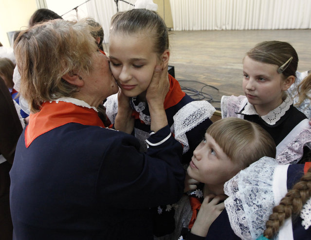 A veteran kisses children, wearing red neckerchiefs, a symbol of the Young Pioneer Organisation, during a ceremony for the inauguration of 55 newly adopted members on the day of its anniversary at school-lyceum number 12 in Russia's Siberian city of Krasnoyarsk May 19, 2011. (Photo by Ilya Naymushin/Reuters)
