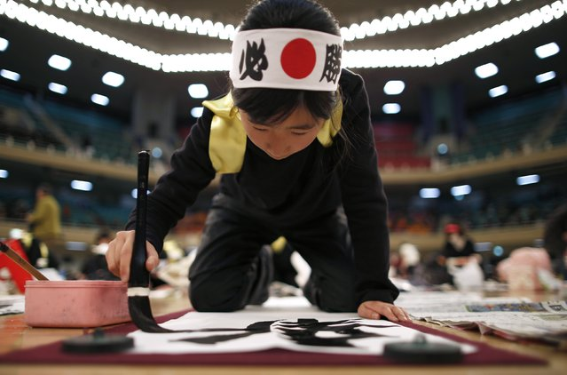 A Japanese girl participates in a calligraphy contest to the celebrate the New Year in Tokyo January 5, 2015. Over 3,000 calligraphers, having qualified in country wide competitions throughout Japan, took part in the annual contest to celebrate the new year. (Photo by Issei Kato/Reuters)