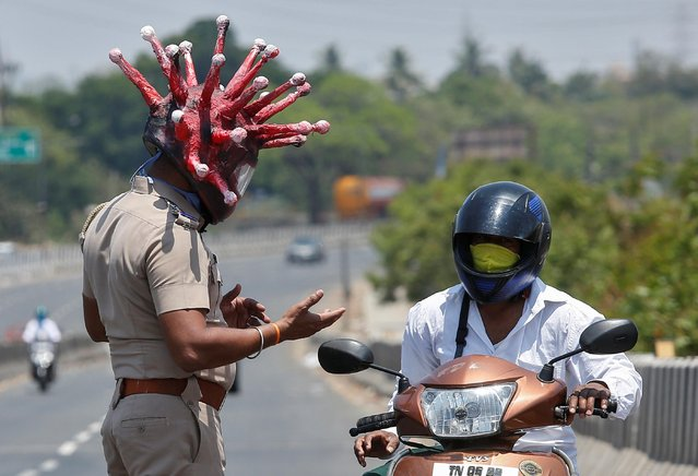 Rajesh Babu, a police officer, wearing a helmet depicting coronavirus, requests a commuter to stay at home during a 21-day nationwide lockdown to limit the spreading of coronavirus disease (COVID-19), in Chennai, India, March 28, 2020. (Photo by P. Ravikumar/Reuters)