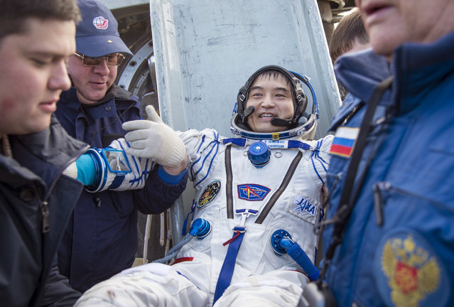 In this photo released by NASA,  Astronaut Takuya Onishi of the Japan Aerospace Exploration Agency (JAXA) is helped out of the Soyuz MS-01 spacecraft just minutes after the NASA astronaut Kate Rubins, and Russian cosmonaut Anatoly Ivanishin of Roscosmos landed in a remote area near the town of Zhezkazgan, Kazakhstan Sunday, October 30, 2016. (Photo by Bill Ingalls/NASA via AP Photo)