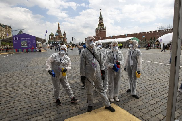 Volunteers wearing face masks, gloves and protective gear to protect against coronavirus, gather to clean an area of an outdoor book market set up at Red Square with GUM, State Department store, left, St. Basil's Cathedral, center, Spasskaya Tower, second with, and the Kremlin Wall, right, in Moscow, Russia, Saturday, June 6, 2020. Muscovites clad in face masks and gloves ventured into Red Square for an outdoor book market, a small sign of the Russian capital's gradual efforts to open up amid coronavirus concerns. (Photo by Alexander Zemlianichenko/AP Photo)