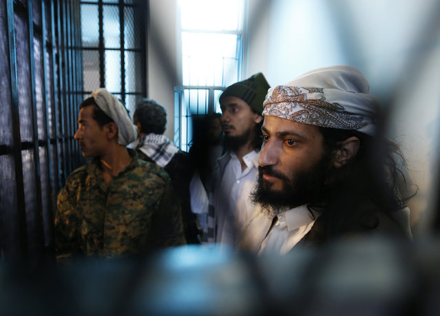 Defendants look out from behind bars as they stand in the holding cell of the state security court in Sanaa December 2, 2014. (Photo by Khaled Abdullah/Reuters)