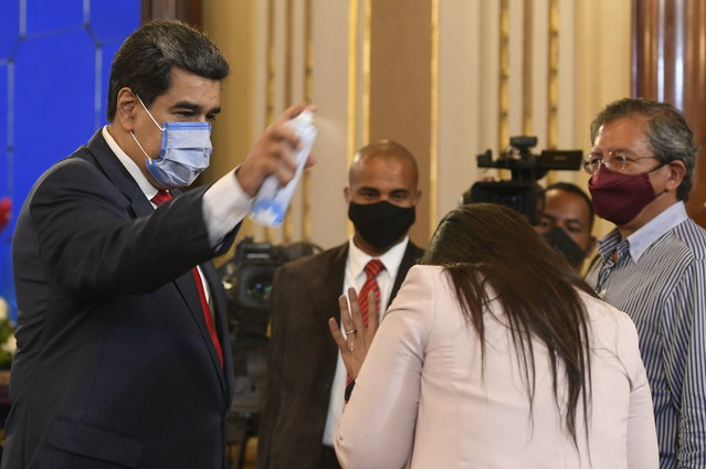 In this December 8, 2020 file photo, Venezuela's President Nicolas Maduro playfully sprays a journalist with disinfectant as he exits a press conference at Miraflores Presidential Palace in Caracas, Venezuela, amid the new coronavirus pandemic. Attorneys for the cash-strapped government blame the impact of U.S. sanctions for its inability to make an initial $18 million down payment to the United Nations for doses of the U.N.-supplied vaccines, whose deadline has already passed. (Photo by Matias Delacroix/AP Photo/File)