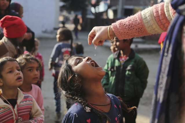 A health worker administers polio drops to children at a government school in a slum area in Jammu, India, Sunday, January 31, 2021. Polio is a highly infectious disease that spreads in contaminated water or food and usually strikes children under 5. (Photo by Channi Anand/AP Photo)