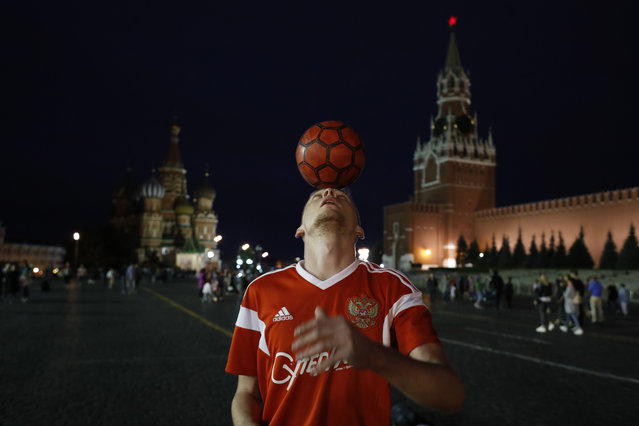 A Russian soccer fan shows off his ball skills as he plays with tourists and soccer fans in Red Square during the 2018 soccer World Cup in Moscow, Russia, Tuesday, July 3, 2018. (Photo by Hassan Ammar/AP Photo)