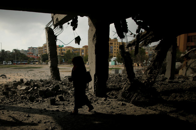A Palestinian woman passes a building that was destroyed by Israeli air strikes in Gaza City July 15, 2018. (Photo by Suhaib Salem/Reuters)