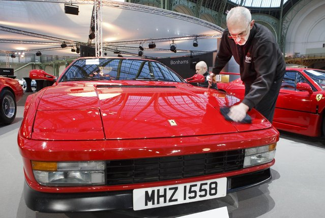 A worker cleans aFerrari Testarossa coupe 1989, during an exhibition, at the Grand Palais in Paris, Wednesday, February 4, 2015. (Photo by Jacques Brinon/AP Photo)