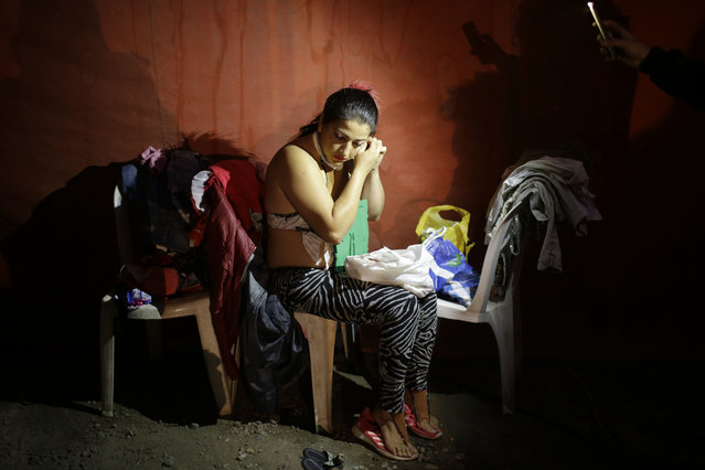 In this July 20, 2018 photo, equilibrist Gladys Melendez, the mother of a 2-year-old daughter, gets ready for the opening act at the International Circus set up in the shantytown of Pro on the outskirts of Lima, Peru. The mom-and-pop style spectacle is one of about a hundred remaining circuses that manage to eke out a living in an age of viral internet videos and cellphones. (Photo by Martin Mejia/AP Photo)