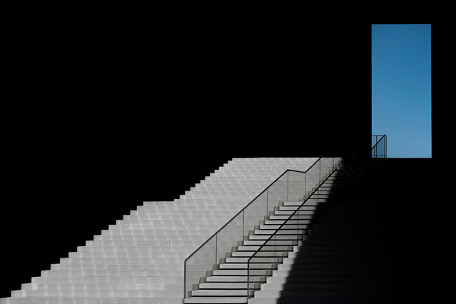 Category winner, open competition, architecture. The Blue Window, depicting a ramp of stairs at the Hyatt hotel in Düsseldorf, Germany, ascending towards a window from which a view of clear blue skies is reflected. Seemingly floating in space, the stairs and window are framed in dark shadows that highlight the design while also adding an element of surrealism. (Photo by Klaus Lenzen/Sony World Photography Awards)