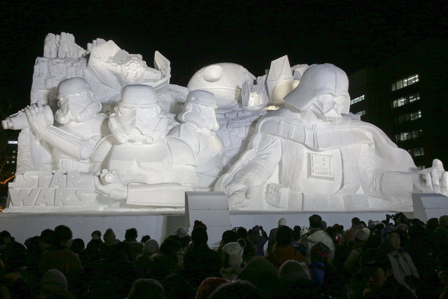 Visitors take picures of a snow sculpture of depicting Star Wars displayed at the 66th Sapporo Snow Festival venue at Odori Park in Sapporo, northern Japan, February 5, 2015, the opening day of the mid-winter festival. The snow festival is held through February 11 and 204 snow and ice sculptures are displayed at three venues, mainly at Odori Park. (Photo by Kimimasa Mayama/EPA)