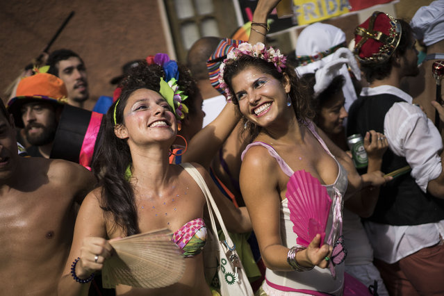 "Revelers dance during the ""Ceu na Terra"", or Heaven on earth, carnival parade in Rio de Janeiro, Brazil, Saturday, February 7, 2015. Rio's over-the-top Carnival is the highlight of the year for many local residents. Hundreds of thousands of merrymakers are beginning to take to the streets in open-air ""blocos"" parties. (Photo by Felipe Dana/AP Photo)"