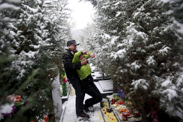 "Fan Guohui comforts his wife Zheng Qing as they show their son's resting place to reporters on their visit to the graveyard in Zhangjiakou, China, November 22, 2015. Fan Lifeng, the son of Fan Guohui and his wife Zheng Qing, both aged 56, was born in 1984 and died in a car accident in 2012. Fan Guohui has petitioned the government to give financial and moral support to ""shidu"" parents, those whose only child had died. Zheng Qing said the couple was ""emotionally ruined"". (Photo by Kim Kyung-Hoon/Reuters)"