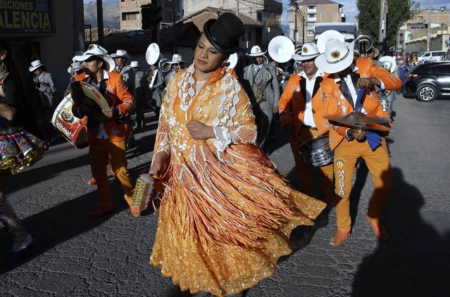 """In this Sunday, August 5, 2018 photo, transgender Jessi dressed as a """"chola"""" dances in the """"Morenada"""" or Dance of the Black Slaves, during celebrations honoring Our Lady of Copacabana, in Cuzco, Peru. Jessi and her friends say they dance in hope their celebratory tribute will help ward off violence and harassment in a country where being transgender can prove deadly. (Photo by Martin Mejia/AP Photo)"""