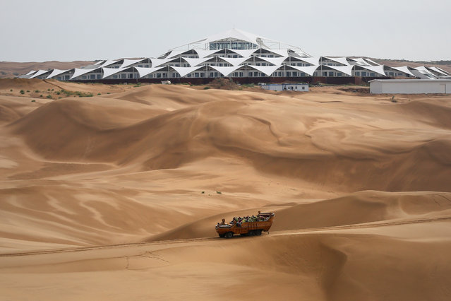 Tourists ride past the Desert Lotus Hotel under construction in Xiangshawan Desert, also called Sounding Sand Desert on July 17, 2013 in Ordos of Inner Mongolia Autonomous Region, China. Xiangshawan is China's famous tourist resort in the desert. It is located along the middle section of Kubuqi Desert on the south tip of Dalate League under Ordos City. Sliding down from the 110-metre-high, 45-degree sand hill, running a course of 200 metres, the sands produce the sound of automobile engines, a natural phenomenon that nobody can explain.  (Photo by Feng Li/Getty Images)