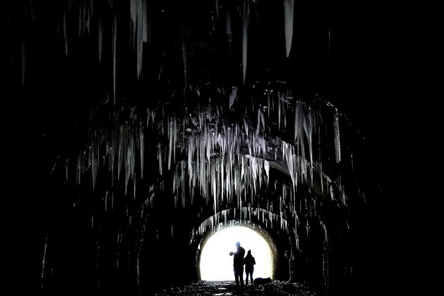 People photograph the icicles hanging from the roof of Hopton Tunnel, near the village of Hopton, Derbyshire, Britain, February 14, 2021. (Photo by Carl Recine/Reuters)