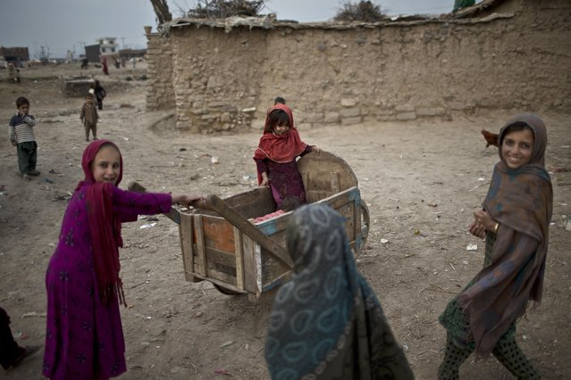Afghan refugee girls play with a wooden-cart in a slum on the outskirts of Islamabad, Pakistan, Friday, February 6, 2015. (Photo by Muhammed Muheisen/AP Photo)
