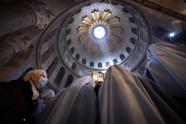 A woman wearing a face mask attends Easter Sunday mass led by Latin Patriarch of Jerusalem Pierbattista Pizzaballa at the Church of the Holy Sepulchre, where Jesus Christ is believed to be buried, in the Old City of Jerusalem, Sunday, April. 4, 2021. (Photo by Oded Balilty/AP Photo)