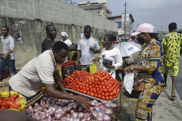 People buy vegetables, at a market in Lagos, Nigeria, Thursday December 24, 2020. Africa's top public health official says another new variant of the coronavirus appears to have emerged in Nigeria, but further investigation is needed. The discovery could add to new alarm in the pandemic after similar variants were announced in recent days in Britain and South Africa and sparked the swift return of travel restrictions. (Photo by Sunday Alamba/AP Photo)