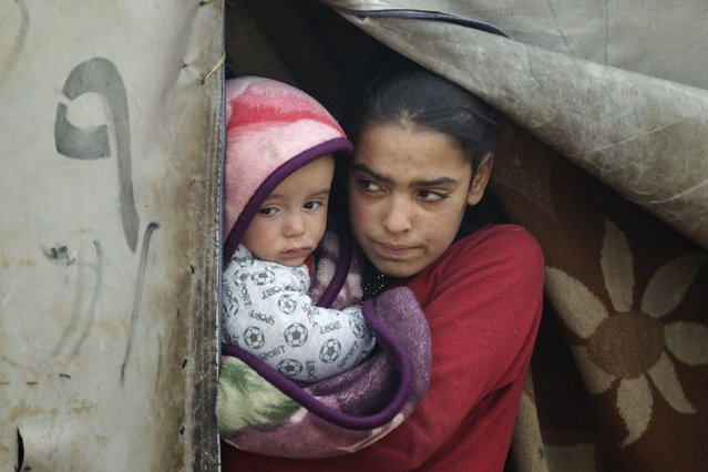 A girl carries her brother as she stands at the entrance of her tent during the cold weather in Jerjnaz camp,for internally displaced people, in Idlib province, Syria, January 5, 2016. (Photo by Khalil Ashawi/Reuters)