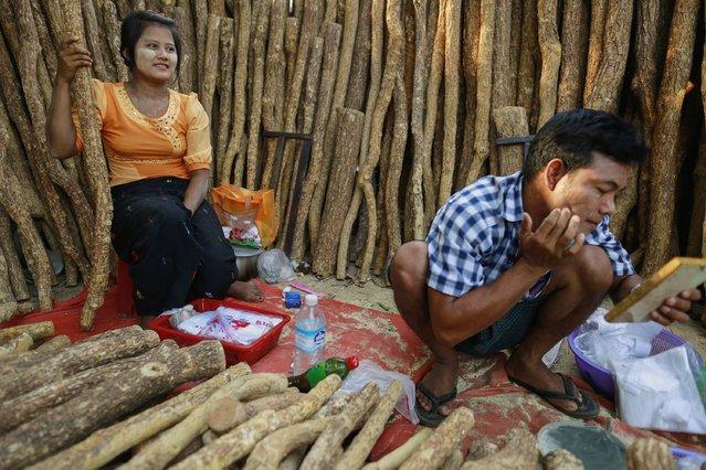 A man applies Thanakha on his face while selling Thanakha wood at the Kyaik-Khauk pagoda festival in Tanlyin township, outside Yangon, February 2, 2015. (Photo by Soe Zeya Tun/Reuters)