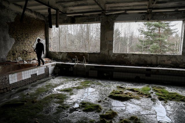 A man walks near the pool in abandoned city of Prypyat, near Chernobyl, Ukraine, 15 April 2021. Ukraine will mark the 35th anniversary of Chernobyl tragedy on 26 April 2021. The explosion of reactor 4 of the Chernobyl nuclear power plant in the early hours of 26 April 1986 is still regarded as the worst nuclear disaster ever. (Photo by Oleg Petrasyuk/EPA/EFE)