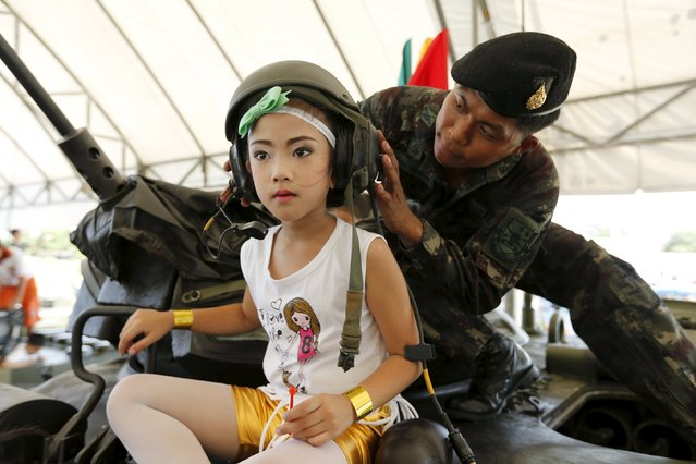 A girl has her helmet adjusted on the top of a tank during the Children's Day celebration at a military facility in Bangkok, Thailand January 9, 2016. (Photo by Jorge Silva/Reuters)