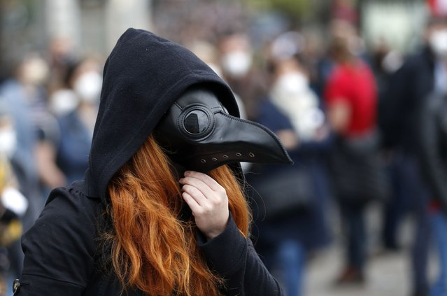 A woman adjusts her mask during a demonstration in Prague, Czech Republic, Thursday, April 29, 2021. Thousands of Czechs have rallied in the capital against President Milos Zeman, accusing him of treason for his pro-Russian stance over the alleged participance of Russian spies in a Czech huge ammunition explosion. (Photo by Petr David Josek/AP Photo)