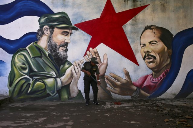 A woman sweeps the Cuba Plaza backdropped by a mural depicting Cuba's former President Fidel Castro and Nicaragua's President Daniel Ortega, in Managua, Nicaragua, Friday, November 4, 2016. (Photo by Esteban Felix/AP Photo)