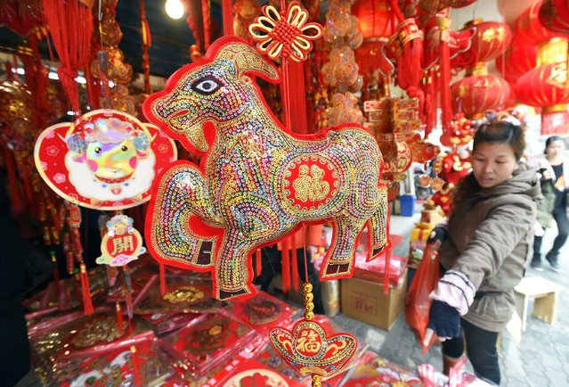 A woman gestures at a stall selling decorations ahead of the upcoming Spring Festival in Wuhan, Hubei province February 16, 2015. (Photo by Reuters/Stringer)