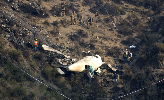 Pakistani investigators examine the wreckage of a passenger plane crashed in the village of Gug, Pakistan Thursday, December 8, 2016. A Pakistani aviation spokesman says authorities have opened a probe into the plane crash in the country's northwest the previous day. (Photo by B.K. Bangash/AP Photo)