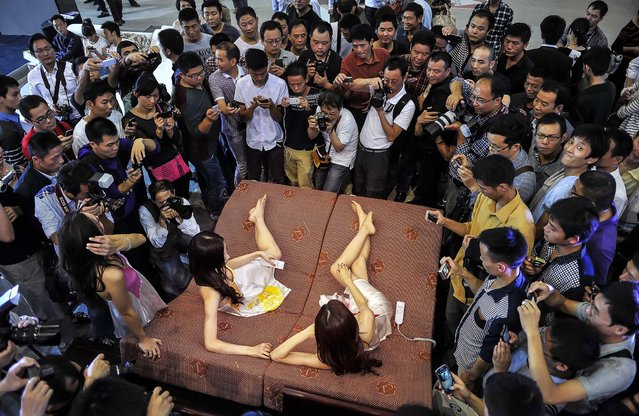 Visitors and journalists take pictures of models, who were promoting mattresses at an automobile exhibition in Hefei, Anhui province, on October 1, 2013. (Photo by Reuters)