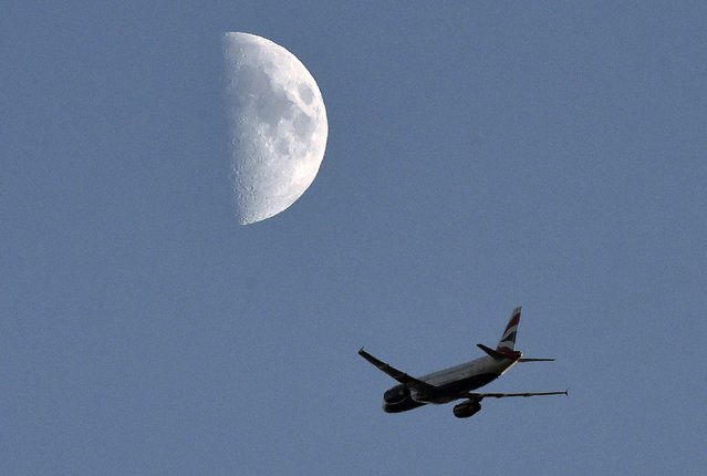 A British Airways passenger plane flies with over the Twickenham Rugby stadium with the moon seen behind in London, November 29, 2014. (Photo by Toby Melville/Reuters)