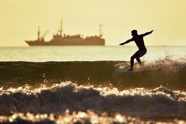 A man enjoys surfing in Sobol Bay, off the coast of Ussuri Bay in Vladivostok, Russia on April 14, 2021. (Photo by Yuri Smityuk/TASS)