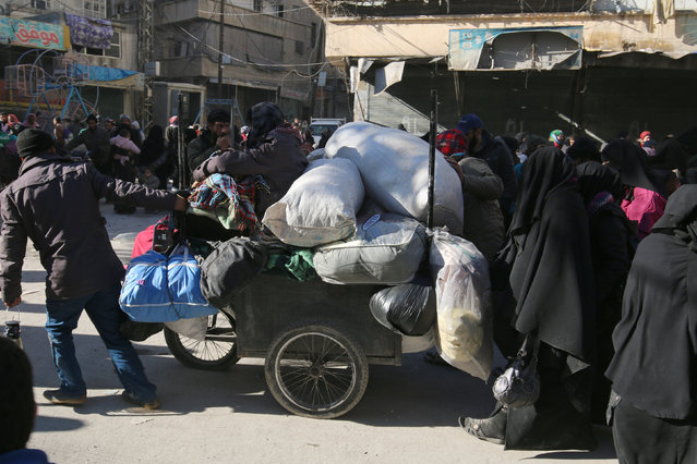 People walk with their belongings as they gather to be evacuated from a rebel-held sector of eastern Aleppo, Syria December 15, 2016. (Photo by Abdalrhman Ismail/Reuters)