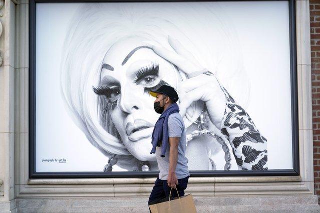 A shopper walks past a mural amid the COVID-19 pandemic on The Promenade Wednesday, June 9, 2021, in Santa Monica, Calif. (Photo by Marcio Jose Sanchez/AP Photo)