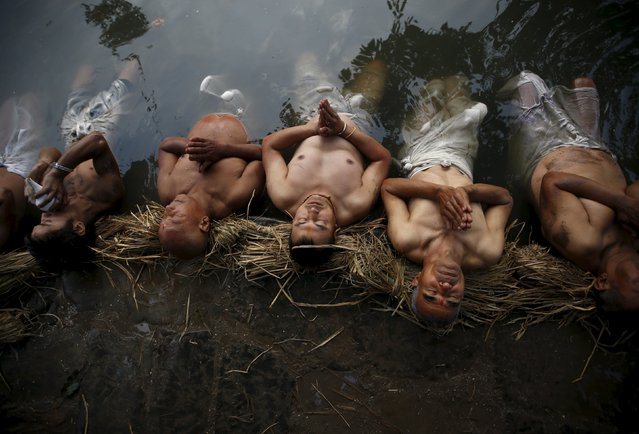 Devotees offer prayers by submerging themselves in the Hanumante River during a month-long Swasthani Brata Katha festival in Bhaktapur, Nepal, January 27, 2016. (Photo by Navesh Chitrakar/Reuters)