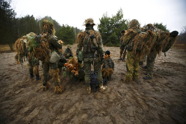 Participiants gather and listen to instructions during a territorial defence training organised by paramilitary group SJS Strzelec (Shooters Association) in the forest near Minsk Mazowiecki, eastern Poland March 14, 2014. (Photo by Kacper Pempel/Reuters)