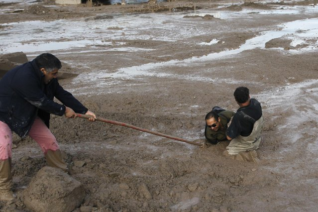 Two men try to help another cross a mud flat in Copiapo, Chile, Thursday, March 26, 2015. Unusually heavy thunder storms and torrential rains that began on Tuesday have blocked roads, caused power outages and affected some 600 people on this normally dry region. (Photo by Aton Chile/Marcelo Hernandez/AP Photo)