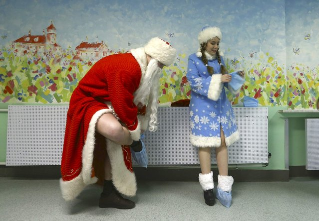 Performers dressed as Ded Moroz, the equivalent of Santa Claus, and his granddaughter Snegurochka (Snow Maiden) take on shoe covers as they visit the Republican Scientific and Practical Centre of Pediatric Surgery in Minsk, Belarus, December 28, 2016. (Photo by Vasily Fedosenko/Reuters)