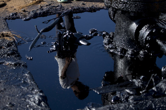 In this August 20, 2018 photo, a boy is reflected in a puddle of crude spilling from a well in Cabimas on the outskirts of Maracaibo, Venezuela. Broken down oil platforms span the vast Maracaibo Lake, with downwind shores soaked in oil. (Photo by Fernando Llano/AP Photo)