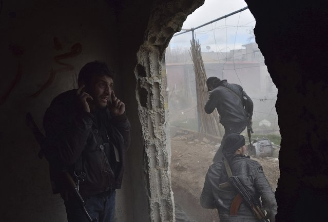 A rebel fighter from the Free Syrian Army's Al Rahman legion covers his ears during the launching of a mortar at the frontline against forces loyal to Syria's President Bashar al-Assad in the besieged town of Arbeen in the eastern Ghouta of Damascus February 19, 2015. (Photo by Yousef Homs/Reuters)